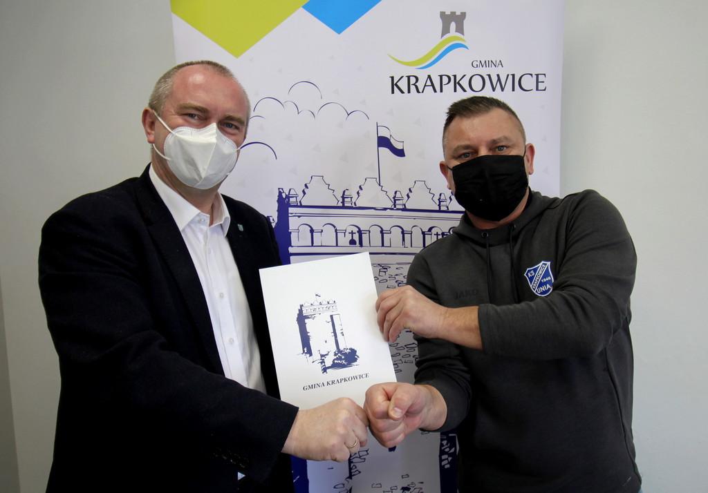 Burmistrz Krapkowic Andrzej Kasiura i prezes klubu KS unia Krapkowice prezentują podpisaną umowę.