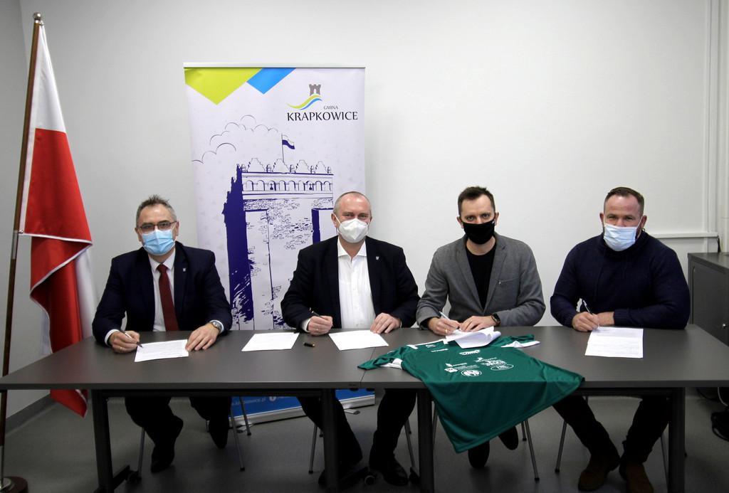 Podpisanie umowy, Arnold Joszko, Andrzej Kasiura, Bartek Banachowski, Daniel Medwid siedzą przy stole. Na stole leży koszulka klubu ks unia Krapkowice.